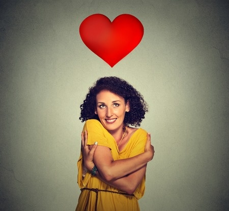 47505575 - closeup portrait smiling woman holding hugging herself with red heart above head isolated gray wall background. positive human emotion, facial expression feeling, attitude. love yourself concept